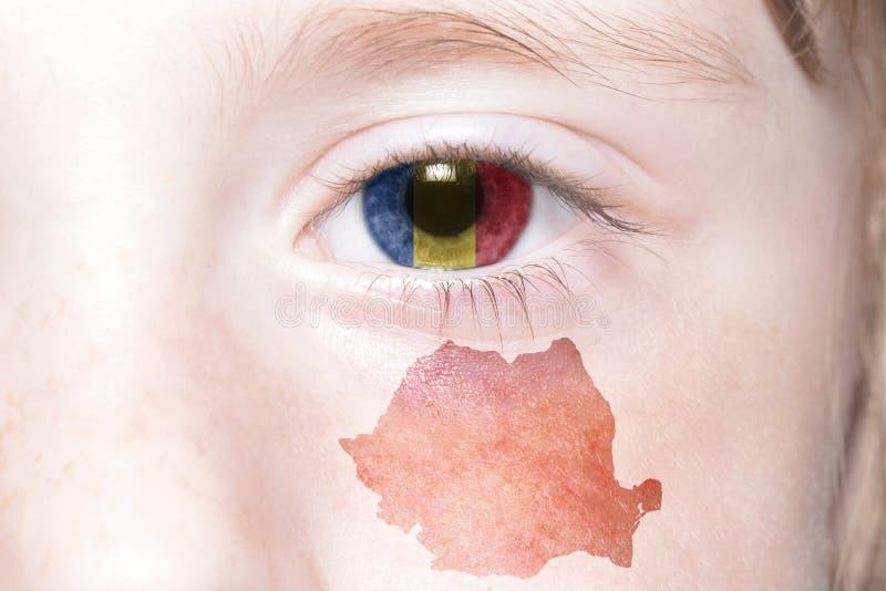 Human& x27 ; visage de s avec le drapeau national et la carte de la Roumanie photos stock