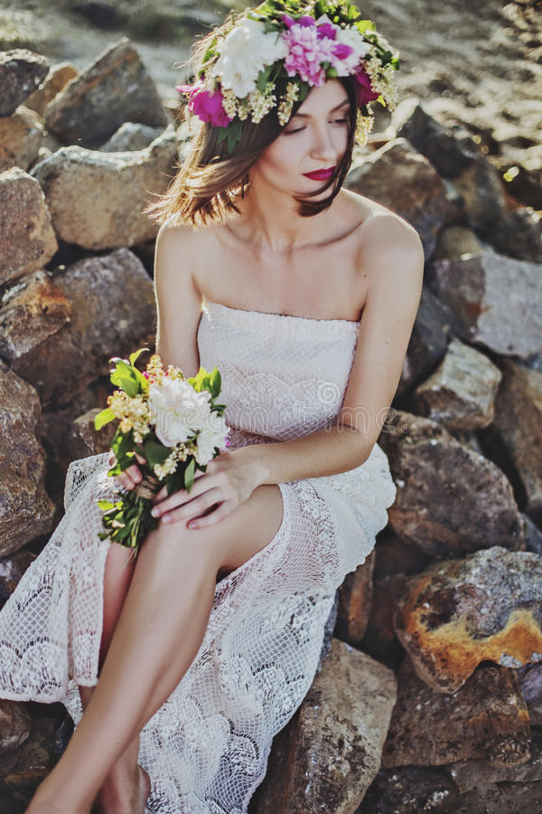 Download Human In White Mesh Strap Less Dress Sitting On Brown Rocks Stock Photo - Image of female, stock: 83015532