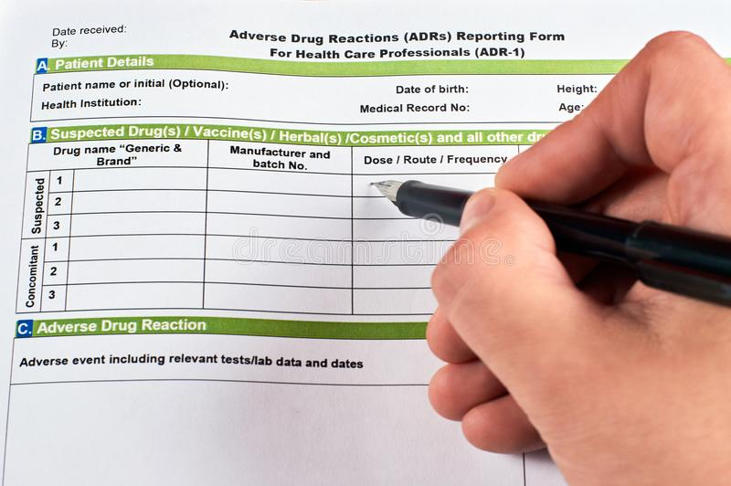 Adverse drug reaction reporting form. Human writes in adverse drug reaction reporting form royalty free stock photo