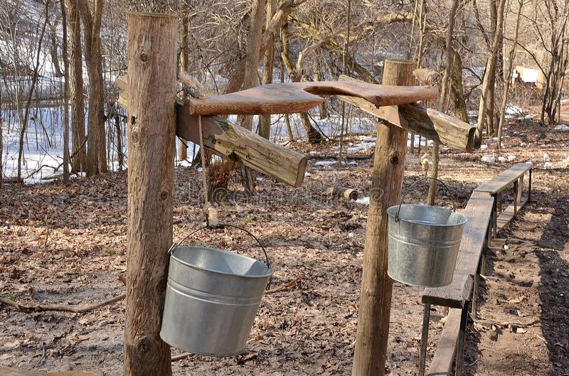 Human yoke on rest with attached buckets for maple syrup
