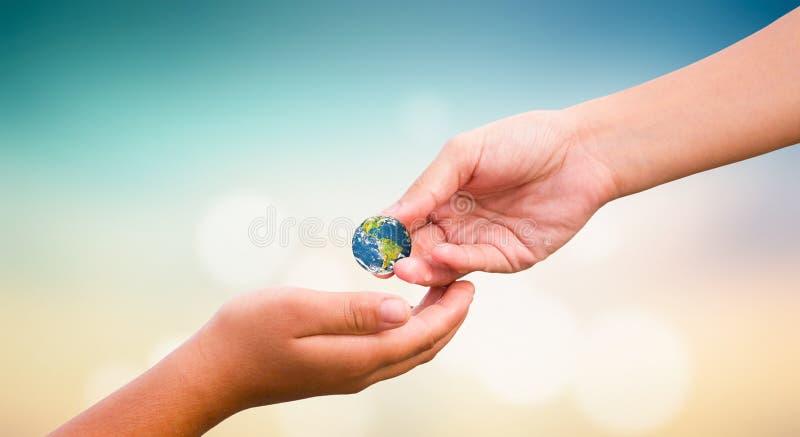 Humanitärt dagbegrepp för värld: hållande jordjordklot för händer över naturlig bakgrund royaltyfria bilder