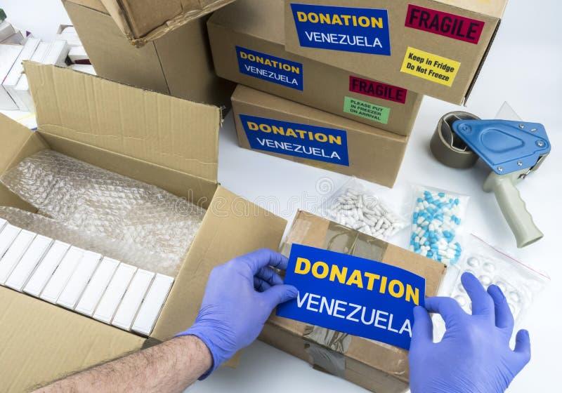 Humanitarian aid, nurse placing label donation medication to send Venezuela. Conceptual image royalty free stock image