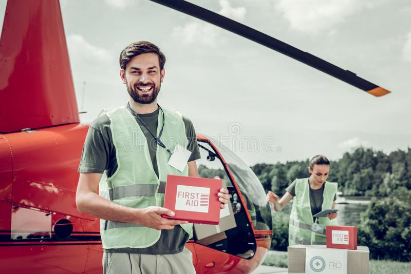 Humanitarian officer standing near little red helicopter with colleague. Near red helicopter. Humanitarian officer standing near little red helicopter with royalty free stock photos
