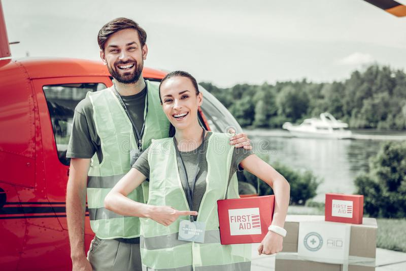 Humanitarian officers sending first aid boxes to military places. To military places. Couple of excited humanitarian officers sending first aid boxes to military royalty free stock images
