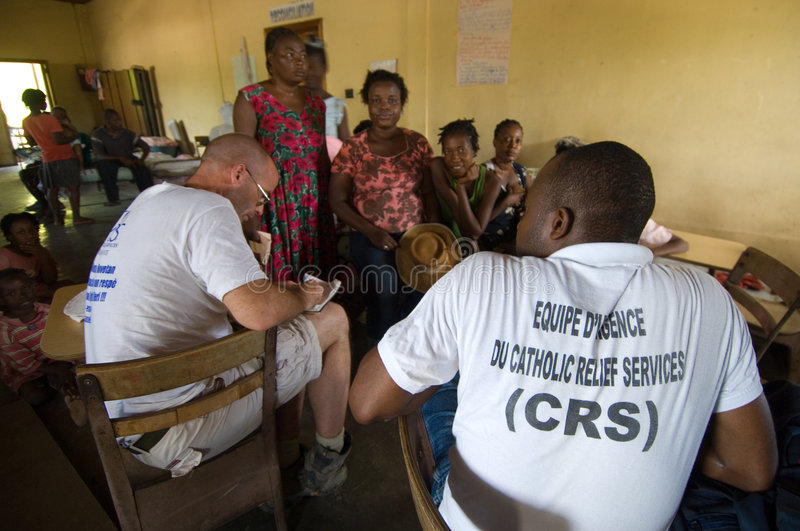 Humanitarian Workers. September 27, 2008 - Aid workers for a humanitarian agency speak with survivors of Hurricane Ike living in a church compound in Gonaives stock image