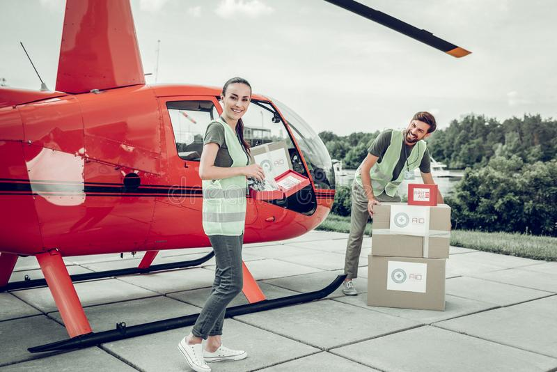 Humanitarian workers standing near helicopter sending parcels. Humanitarian workers. Couple of motivated humanitarian workers standing near helicopter while stock photos