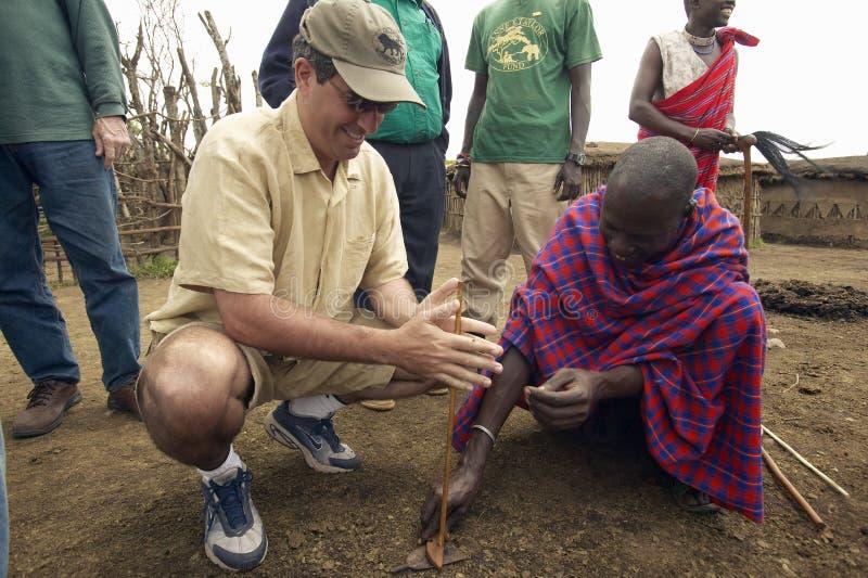 Humanitarny społeczeństwo dyrektor generalny, Wayne Pacelle, uczy się robić ogieniowi od współplemiena blisko Tsavo parka narodow zdjęcia royalty free