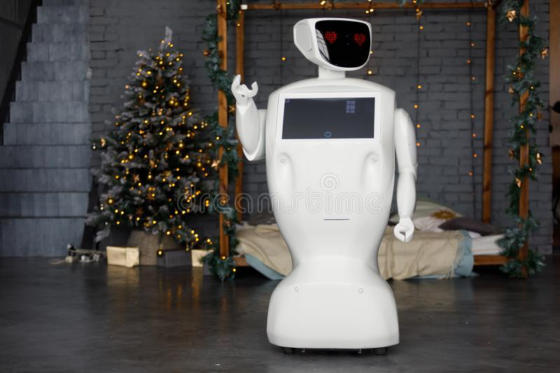 The robot meets Christmas, stands on the background of the garland royalty free stock images