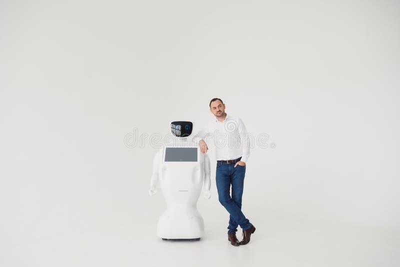 Humanoid autonomous robot with stylish man in a suit. Modern Robotic Technologies. Humanoid autonomous robot. white. Businessman next to a robot. Modern Robotic stock image