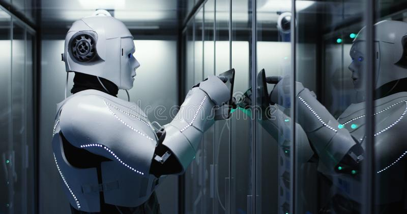 Humanoid robot checking servers in a data center. Medium shot of a humanoid robot checking servers in a data center while holding a tablet stock photos
