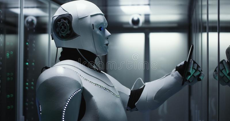 Humanoid robot checking servers in a data center. Medium shot of a humanoid robot checking servers in a data center while holding a tablet royalty free stock image