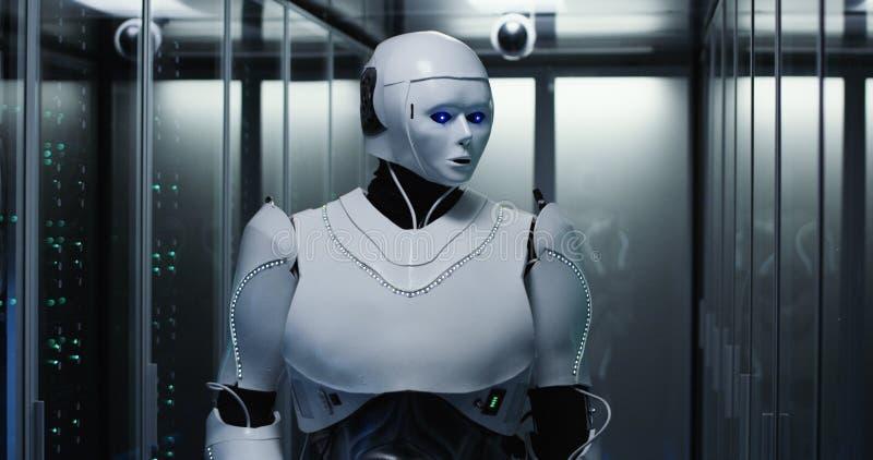 Humanoid robot som kontrollerar serveror i en datorhall arkivfoton