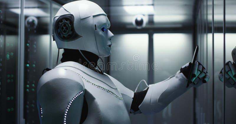 Humanoid robot som kontrollerar serveror i en datorhall royaltyfri bild
