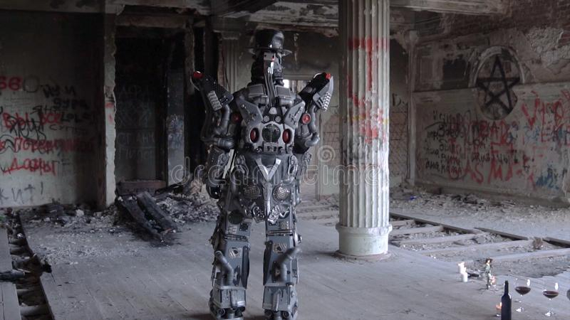Humanoid robot stands with his back in hat in abandoned building. Footage. Android on date with glasses and bottle of stock photo