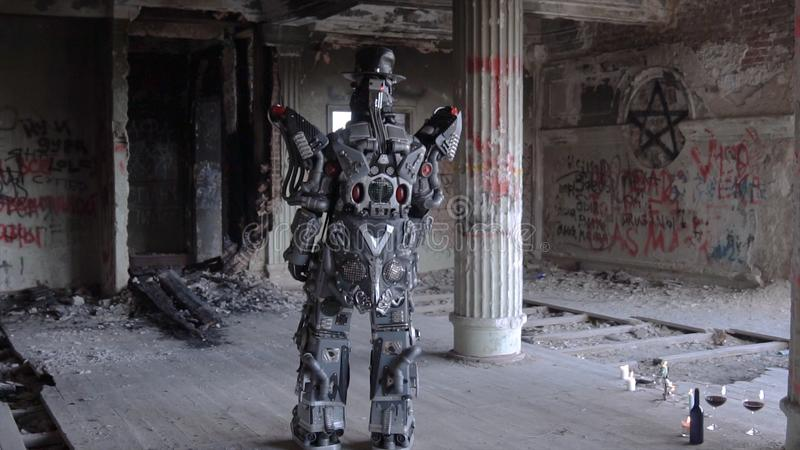 Humanoid robot stands with his back in hat in abandoned building. Footage. Android on date with glasses and bottle of. Wine stands back against gray walls with royalty free stock photo