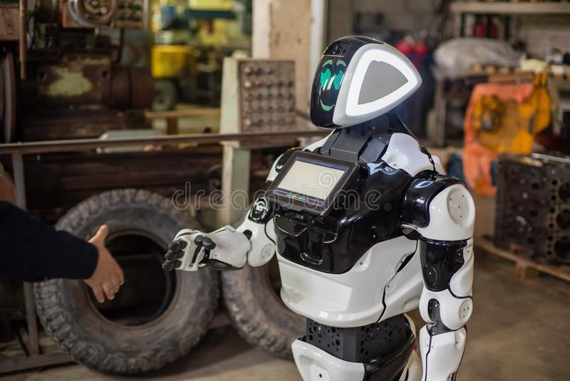 Humanoid robot on wheels with a monitor on his chest, shaking hands with a man. The old cluttered garage. Humanoid robot on wheels with a monitor on his chest stock image