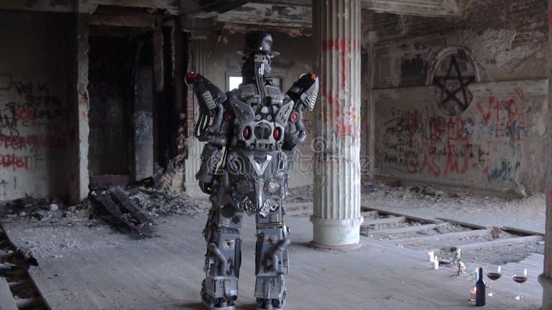 Humanoid Roboter steht mit seinem zurück im Hut in verlassenem Gebäude gesamtlänge Android auf Datum mit Gläsern und Flasche von lizenzfreies stockfoto
