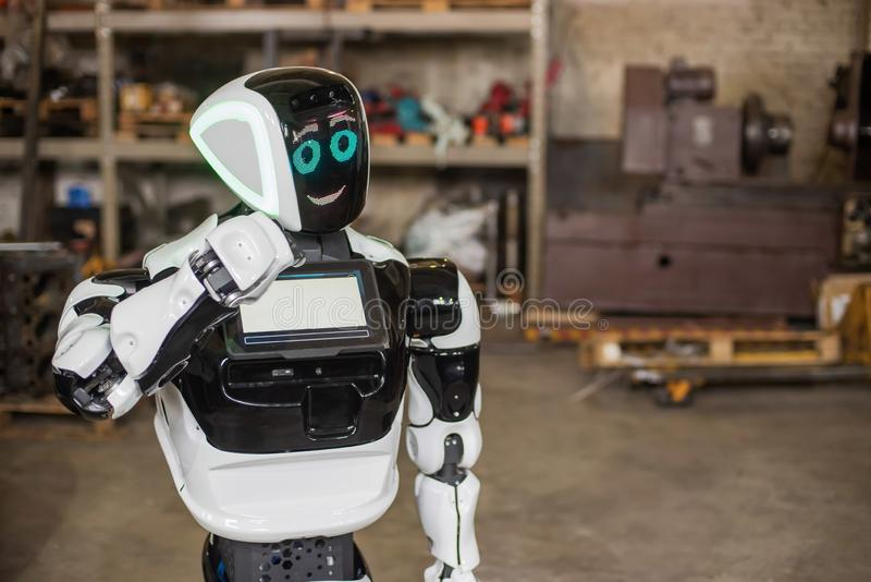 A humanoid, white robot on wheels, with a display on his chest, moves his hands. It stands in a dirty, cluttered garage with old. Machines. Daylight stock photos