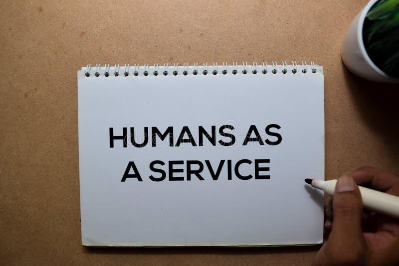 Humans As A Service escreve num livro sobre a tabela de madeira imagem de stock