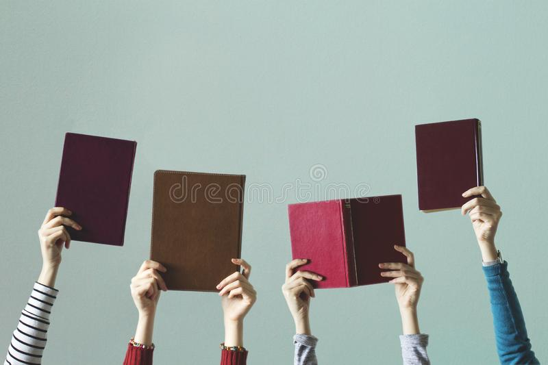Humans holding books in hand. stock photos