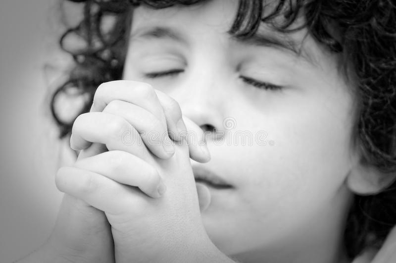 Humble Communication. Hispanic child praying intensely during his Christian daily devotional royalty free stock image