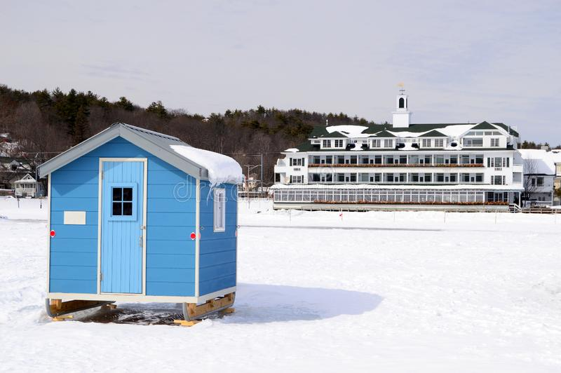 Ice fishing shack on a frozen lake. A humble ice fishing shack contrasts with the luxurious Bay Point at Mill Falls Hotel stock image