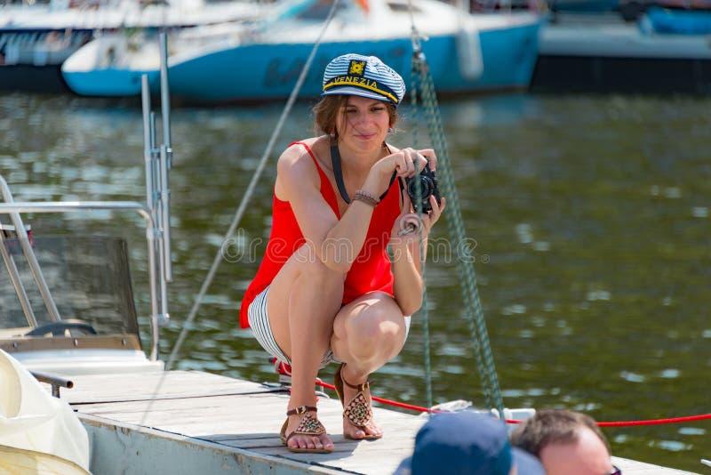 Humeur d'été : une fille dans le chemisier rouge prenant des photos au club de yacht image stock