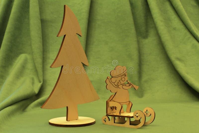Humeur de Noël L'arbre de Noël en bois original, traîneau de cru et un bel ange sur le fond vert photos libres de droits