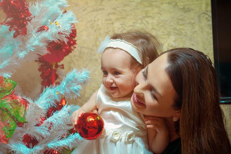 Humeur de Noël La mère décore l'arbre de Noël avec le sien allumé images libres de droits