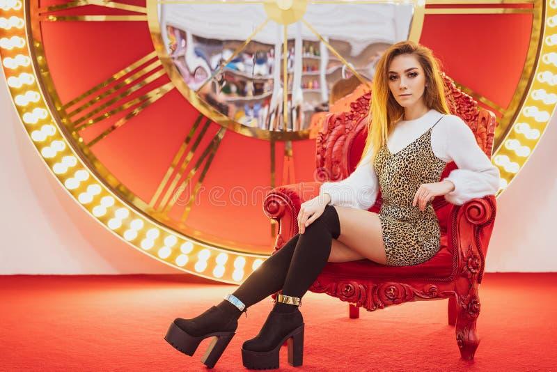 Humeur de sourire de Noël de belle femme se reposant sur une chaise rouge images stock