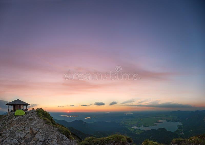 Humeur romantique avec le ciel de coucher du soleil, vue aux collines alpines Bavière, pavillon au dessus de montagne photo libre de droits