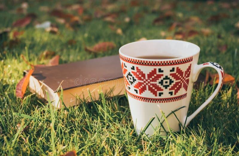 Humeur romantique Le livre fascinant et une tasse chaude de thé parfumé en automne font du jardinage photographie stock