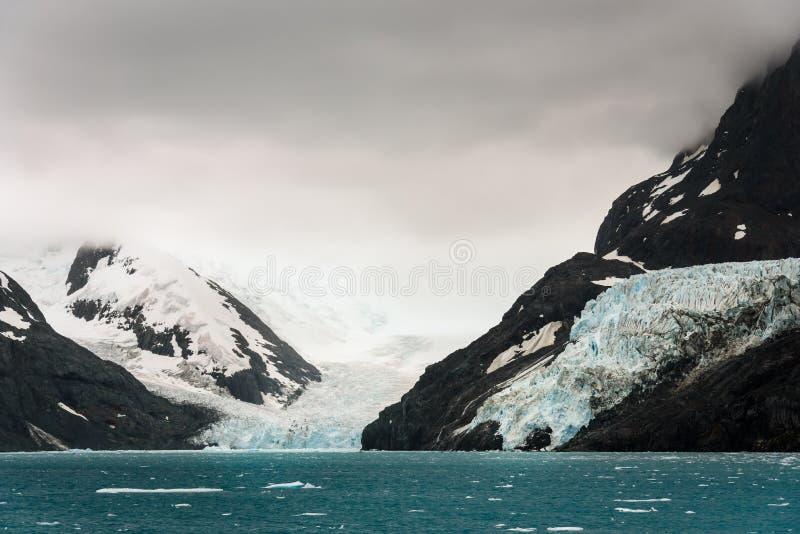 Humeurige die gletsjerscène door sneeuwbergen wordt omringd die in het overzees bij Drygalski-Fjord, Zuid-Georgië voeden royalty-vrije stock afbeeldingen