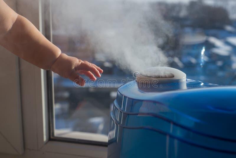 Humidificador produzindo um vapor com uma mão do ` s do bebê foto de stock royalty free