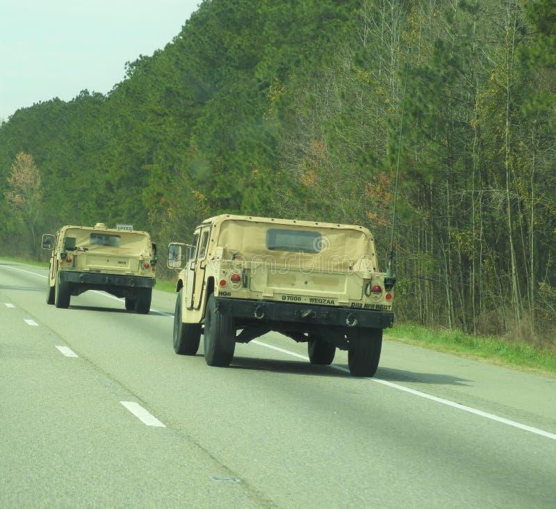 Hummers del ejército que conducen abajo de la autopista imagenes de archivo