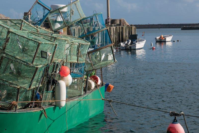 Hummertöpfe gestapelt auf einem Fischerboot in einem Fischereihafen in Portugal lizenzfreie stockfotos