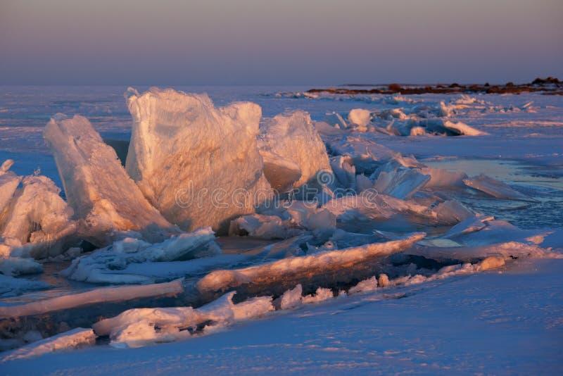 Hummocks de la puesta del sol y del hielo del invierno en el lago foto de archivo libre de regalías