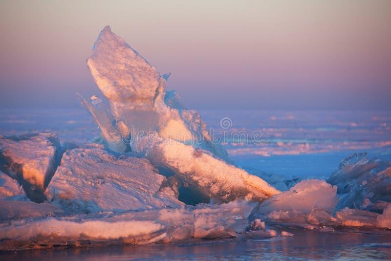 Hummocks di tramonto e del ghiaccio di inverno sul lago fotografie stock libere da diritti