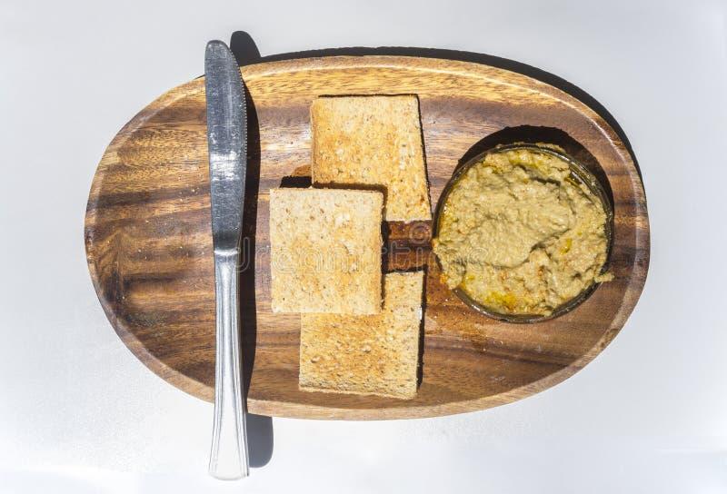Hummus碗用面包干和刀子在木盘子 库存照片