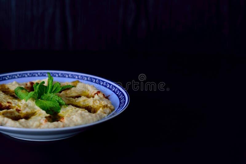 Hummus é um mergulho de Levantine ou a propagação feita dos grãos-de-bico cozinhados, triturados ou do outro café da manhã árabe  foto de stock royalty free