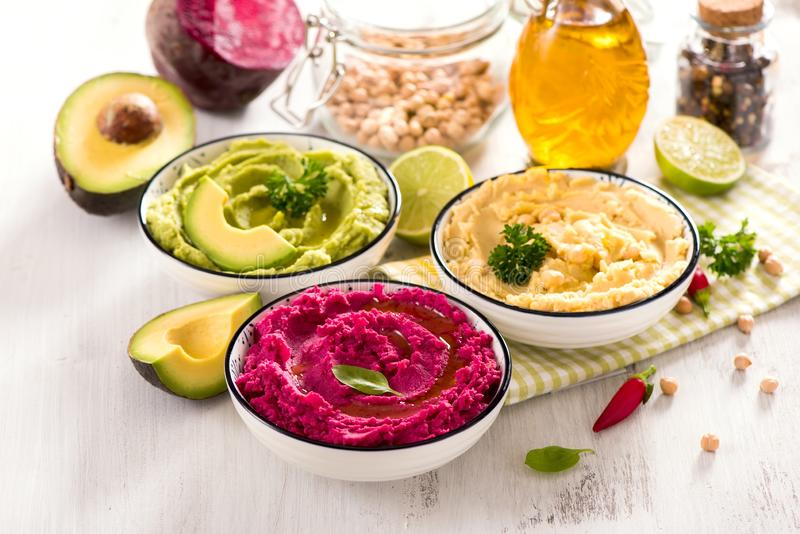 Hummus, ζωηρόχρωμες διαφορετικές εμβυθίσεις, vegan hummus πρόχειρων φαγητών, παντζαριών και αβοκάντο, χορτοφάγος κατανάλωση στοκ φωτογραφία
