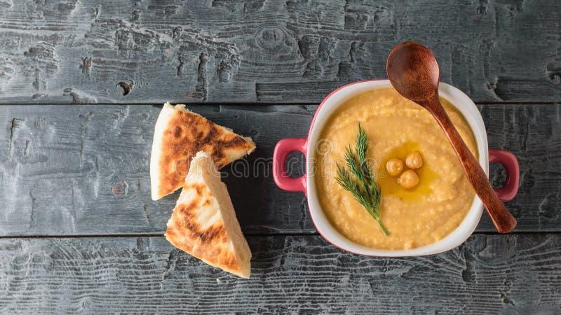 Hummus в фиолетовом шаре с ложкой и 2 кусками темного хлеба на таблице взгляд сверху стоковое фото rf