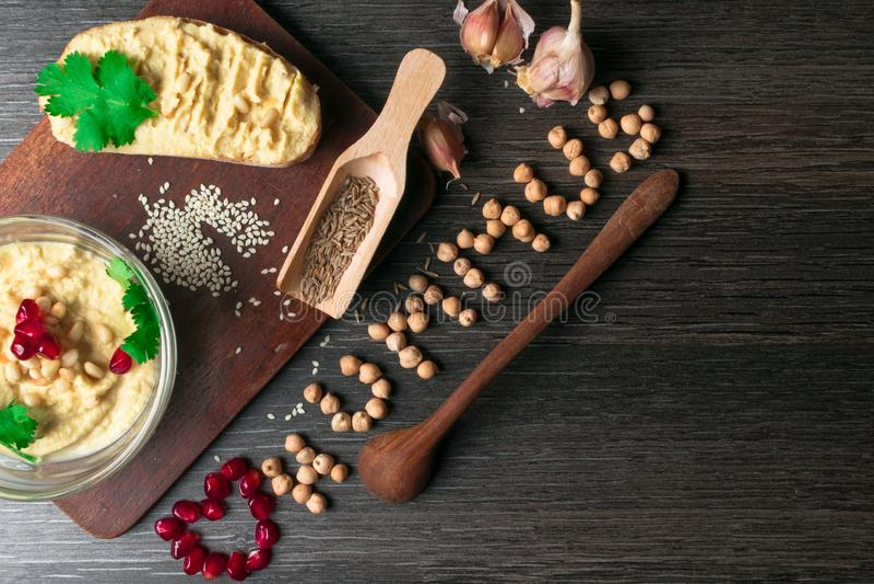 Hummus или houmous, закуска сделанная из помятых нутов с tahini, цитрон, чеснок, оливковое масло, петрушка, тимон и кедр стоковое фото rf