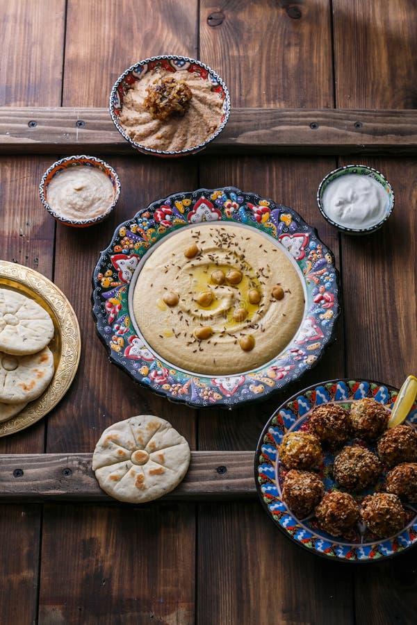 Hummus, нут, falafel с tahini, йогурт и пита в традиционной плите стоковые фото
