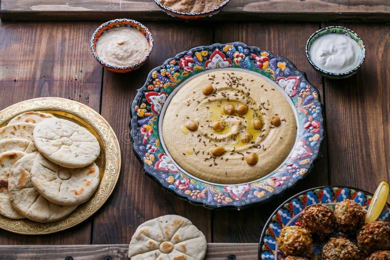 Hummus, нут, falafel с tahini, йогурт и пита в традиционной плите стоковое изображение