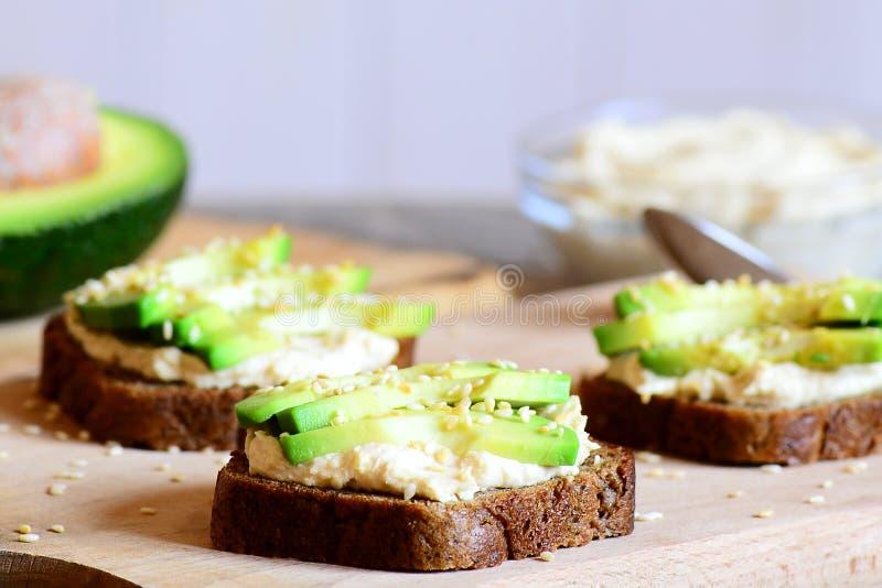 Hummus avocado kanapki na drewnianej desce obrazy royalty free