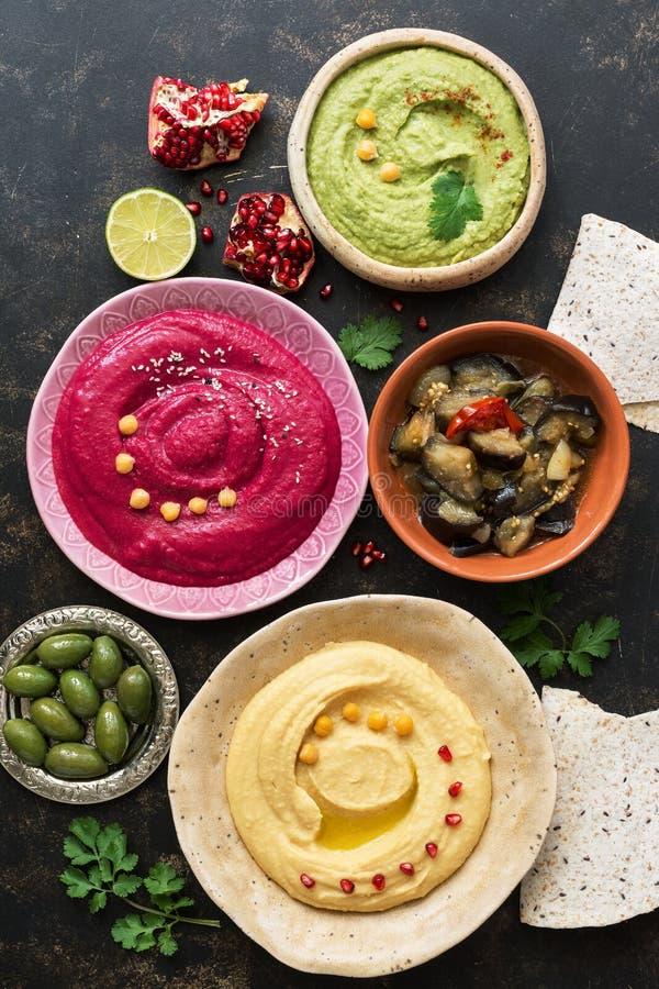 Hummus, caponata, azeitonas, pão árabe e romã variados coloridos em um fundo rústico escuro Vista superior, configuração lisa Ali foto de stock