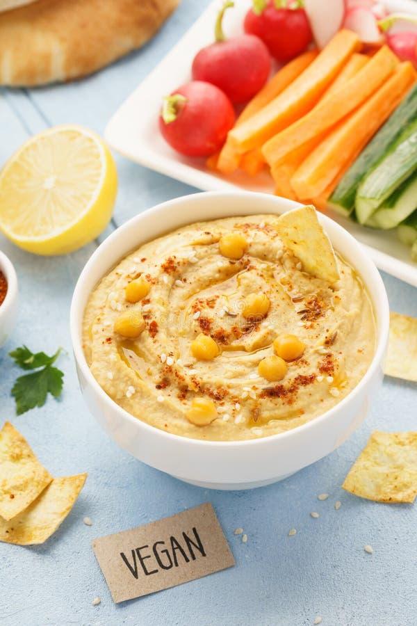 Hummus casalingo con olio d'oliva, i bastoni di verdura fresca ed i chip fotografia stock libera da diritti