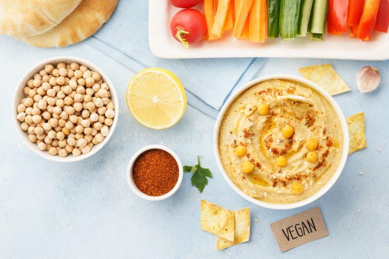 Hummus casalingo con olio d'oliva, i bastoni di verdura fresca ed i chip fotografia stock