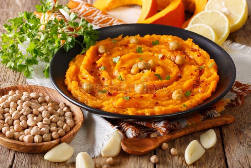 Hummus casalingo della zucca con il primo piano dell'aglio, del limone e del pepe sopra fotografia stock libera da diritti
